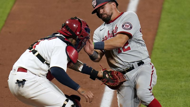Washington Nationals' Kyle Schwarber, right, is tagged out at home by St. Louis Cardinals...