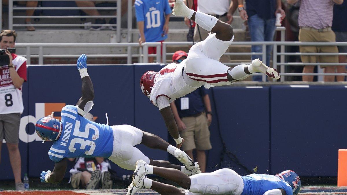 Arkansas quarterback KJ Jefferson (1) is upended by Mississippi linebacker Mark Robinson (35)...