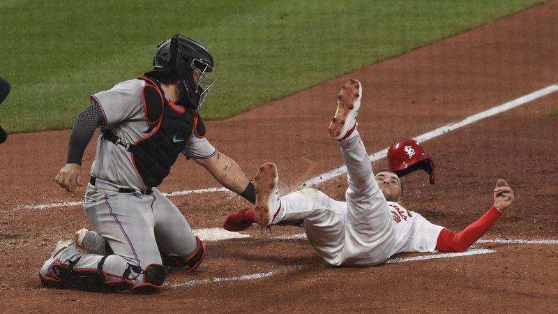Miami Marlins catcher Jorge Alfaro tags out St. Louis Cardinals center fielder Dylan Carlson...