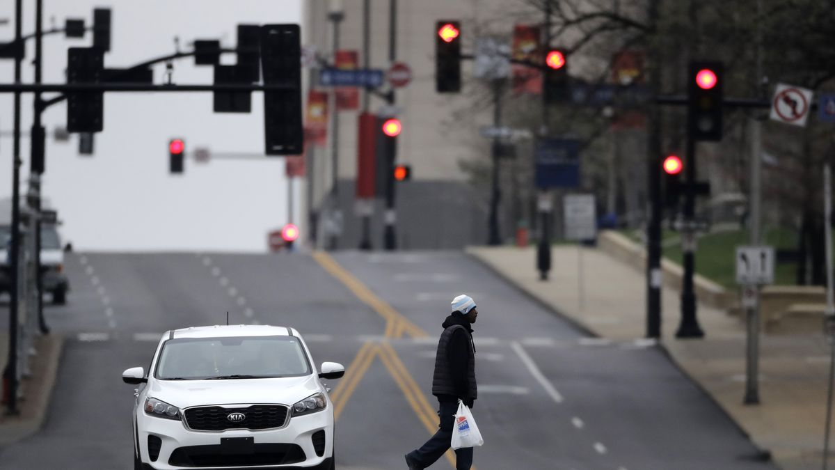 A man carries a bag of groceries through downtown Kansas City, Mo. Sunday, March 22, 2020....