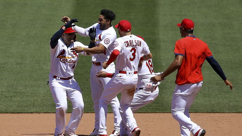 St. Louis Cardinals' Yadier Molina, left, is congratulated by teammates after hitting a...