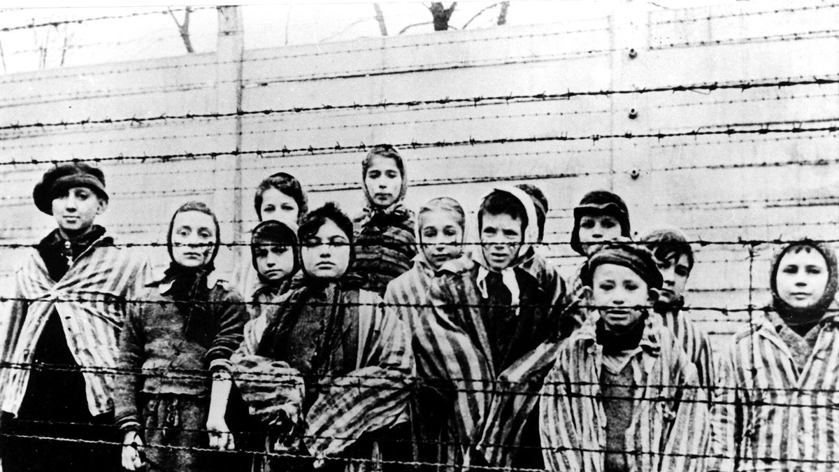 FILE - A picture taken just after the liberation by the Soviet army in January, 1945, shows a group of children wearing concentration camp uniforms at the time behind barbed wire fencing in the Oswiecim (Auschwitz) nazi concentration camp. Germany has agreed to provide more than a half billion euros to aid Holocaust survivors struggling under the burdens of the coronavirus pandemic, the organization that negotiates compensation with the German government said Wednesday. (AP Photo/CAF pap, file)