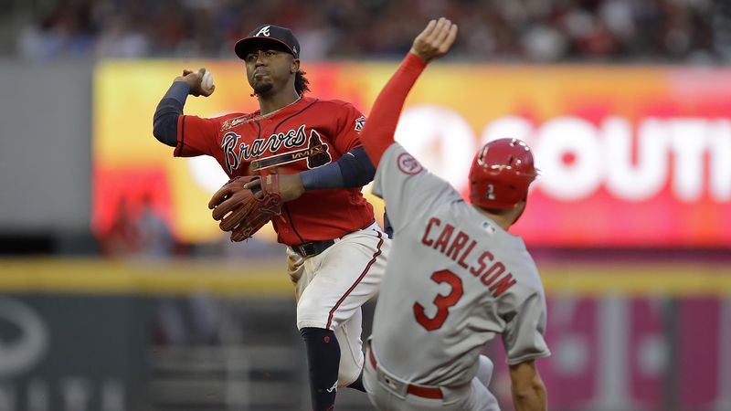 Atlanta Braves' Ozzie Albies, left, prepares his throw to first base to complete a double play...