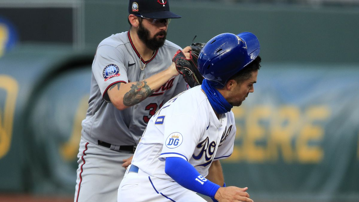 Kansas City Royals' Whit Merrifield, right, is tagged out by Minnesota Twins starting pitcher Devin Smeltzer, left, during a rundown in the first inning of a baseball game at Kauffman Stadium in Kansas City, Mo., Friday, Aug. 7, 2020. (AP Photo/Orlin Wagner)