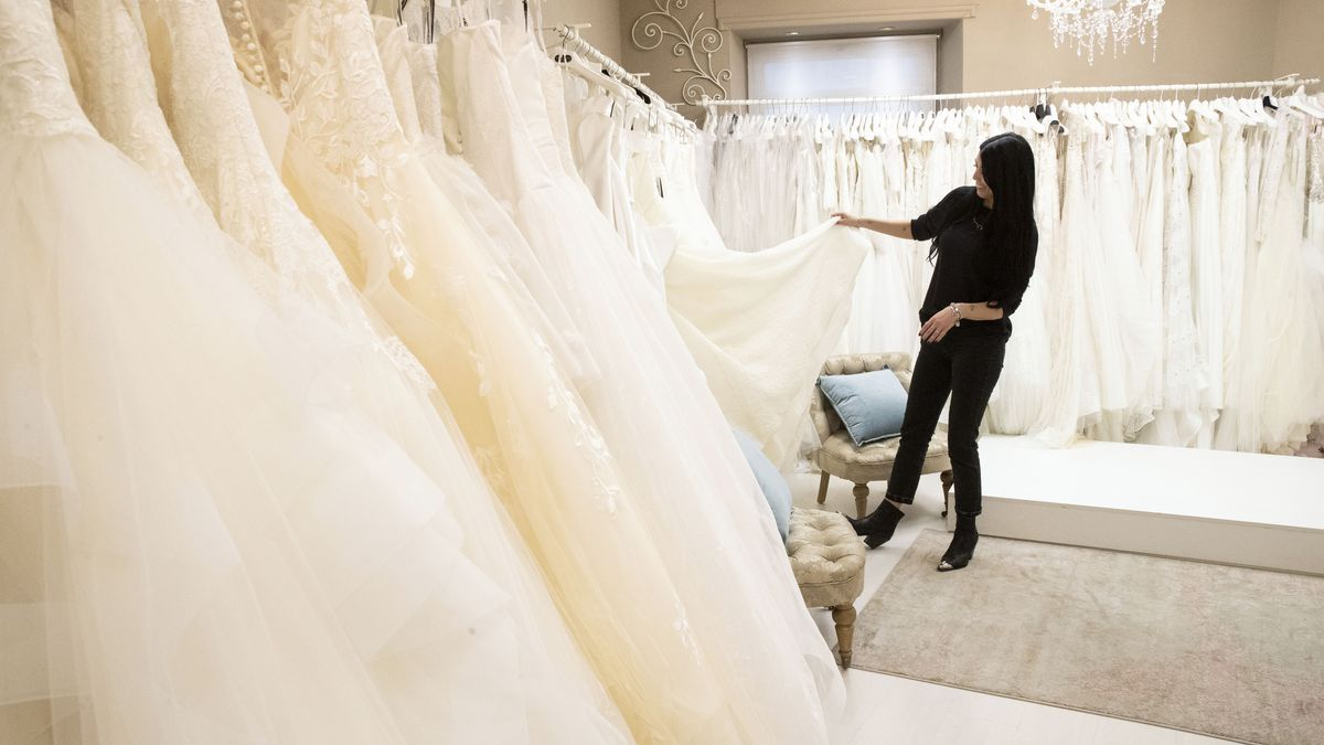 FILE - Anita Galafate checks wedding dresses in a shop in Rome, Tuesday, March 9, 2021. Couples...