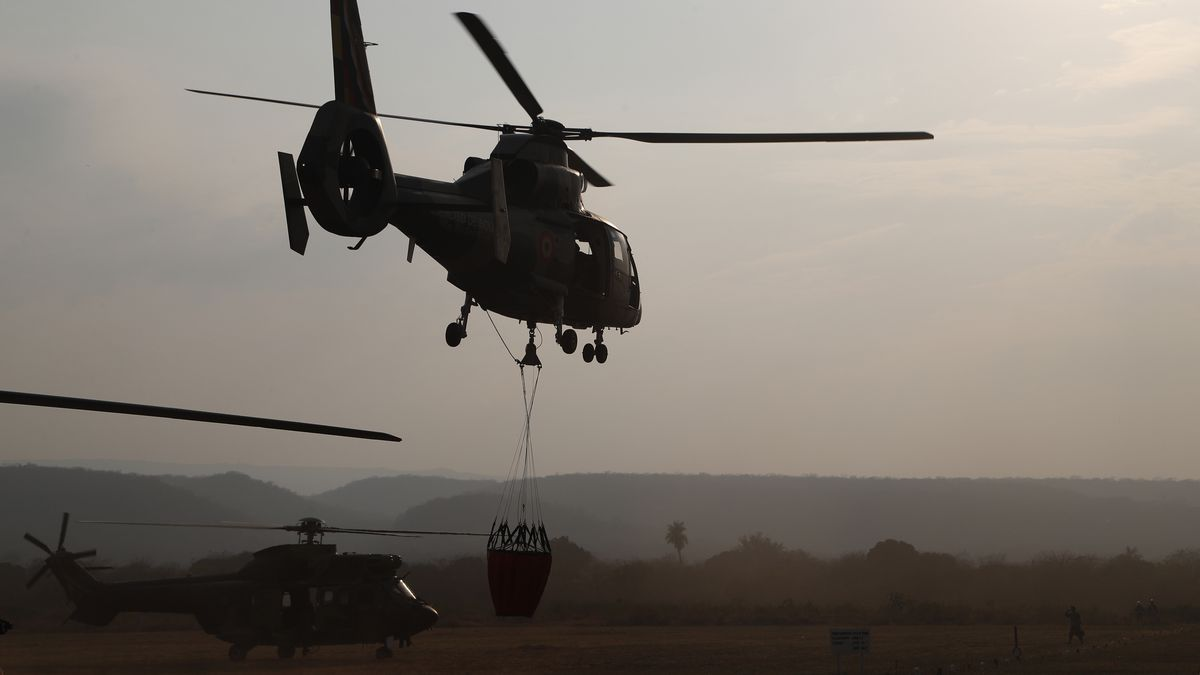 A helicopter lifts off from a military airport Robore, Bolivia, with water to drop on the...