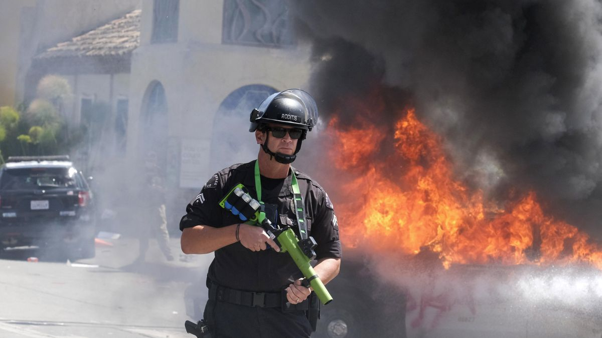 A police officer stands guard while a police vehicle burns during a protest over the death of George Floyd in Los Angeles, Saturday, May 30, 2020. Protests across the country have escalated over the death of George Floyd who died after being restrained by Minneapolis police officers on Memorial Day, May 25.(AP Photo/Ringo H.W. Chiu)