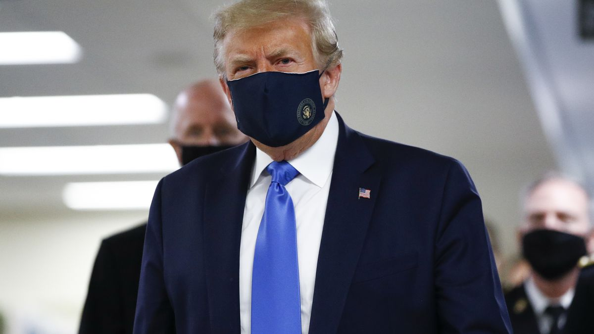 President Donald Trump wears a mask as he walks down the hallway during his visit to Walter...
