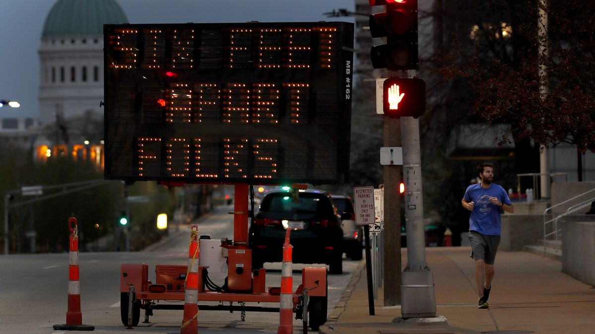FILE - In this April 2, 2020 file photo, a person jogs past a sign encouraging social...