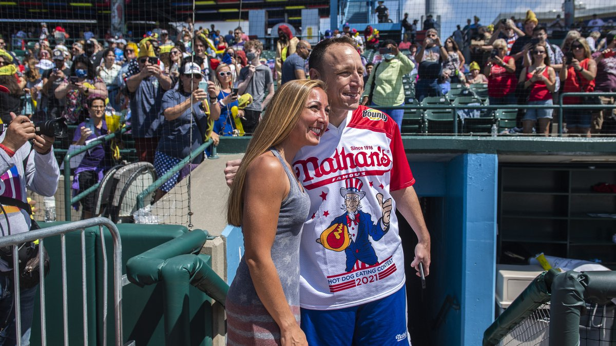 Danielle Diaz, left, takes a photo with Joey Chestnut at the Nathan's Famous Fourth of July...