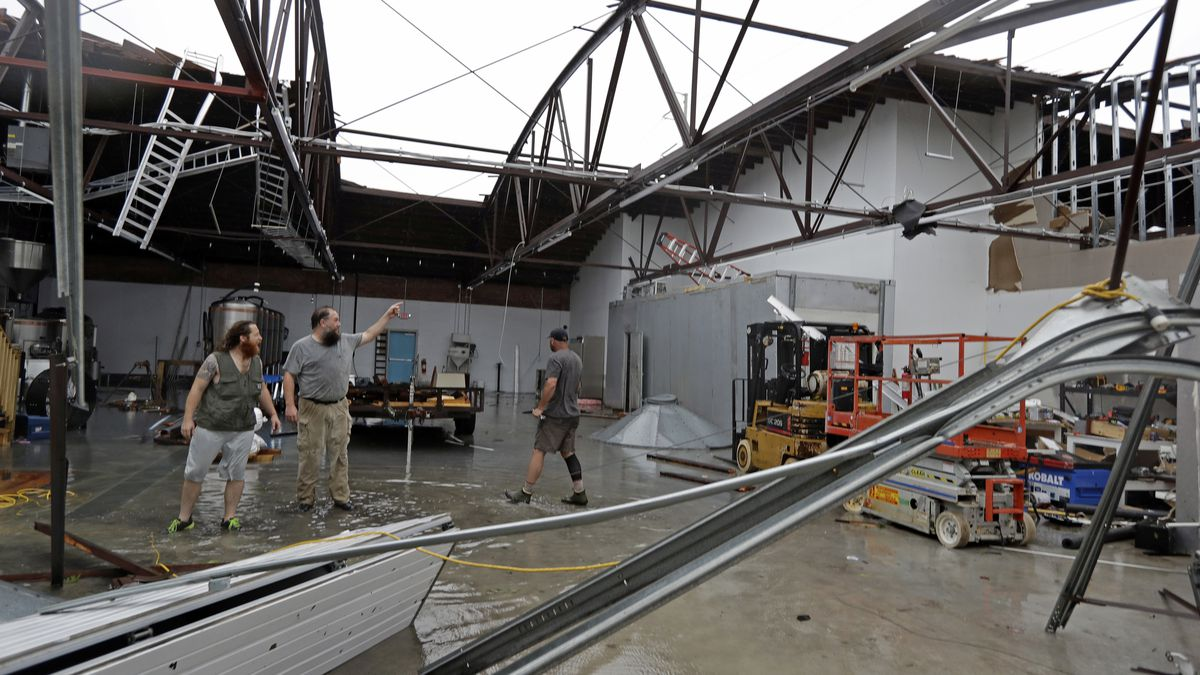 Ethan Hall, right, Michael Jenkins, center, and Nash Fralick, left, examine damage to...