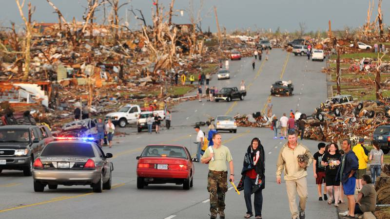 FILE - In this May 22, 2011, file photo residents walk in the street after a massive tornado...