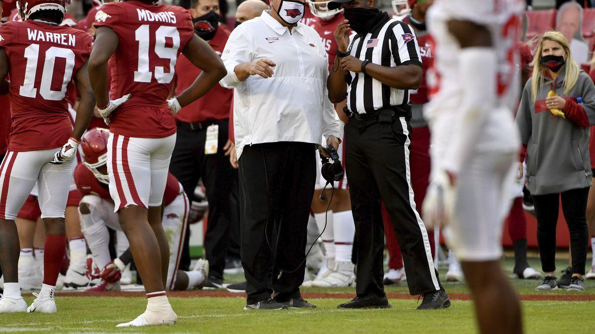 Arkansas coach Sam Pittman, center, talks with an official during the second half of an NCAA...