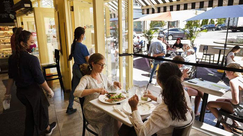 Liz Cahn, center, and her daughter Cara eat lunch at Meli-Melo Creperie, Juice Bar &...