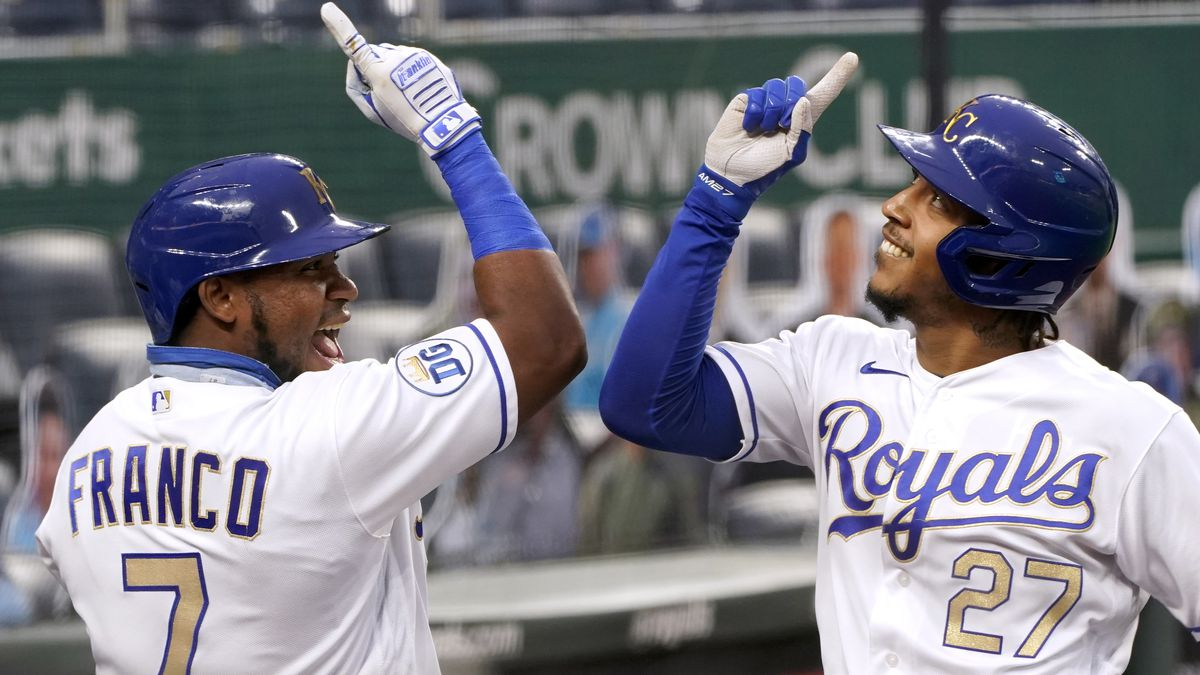 Kansas City Royals' Adalberto Mondesi (27) celebrates with Maikel Franco (7) as he comes into the dugout after hitting a solo home run during the first inning of the team's baseball game against the Pittsburgh Pirates on Friday, Sept. 11, 2020, in Kansas City, Mo. (AP Photo/Charlie Riedel)