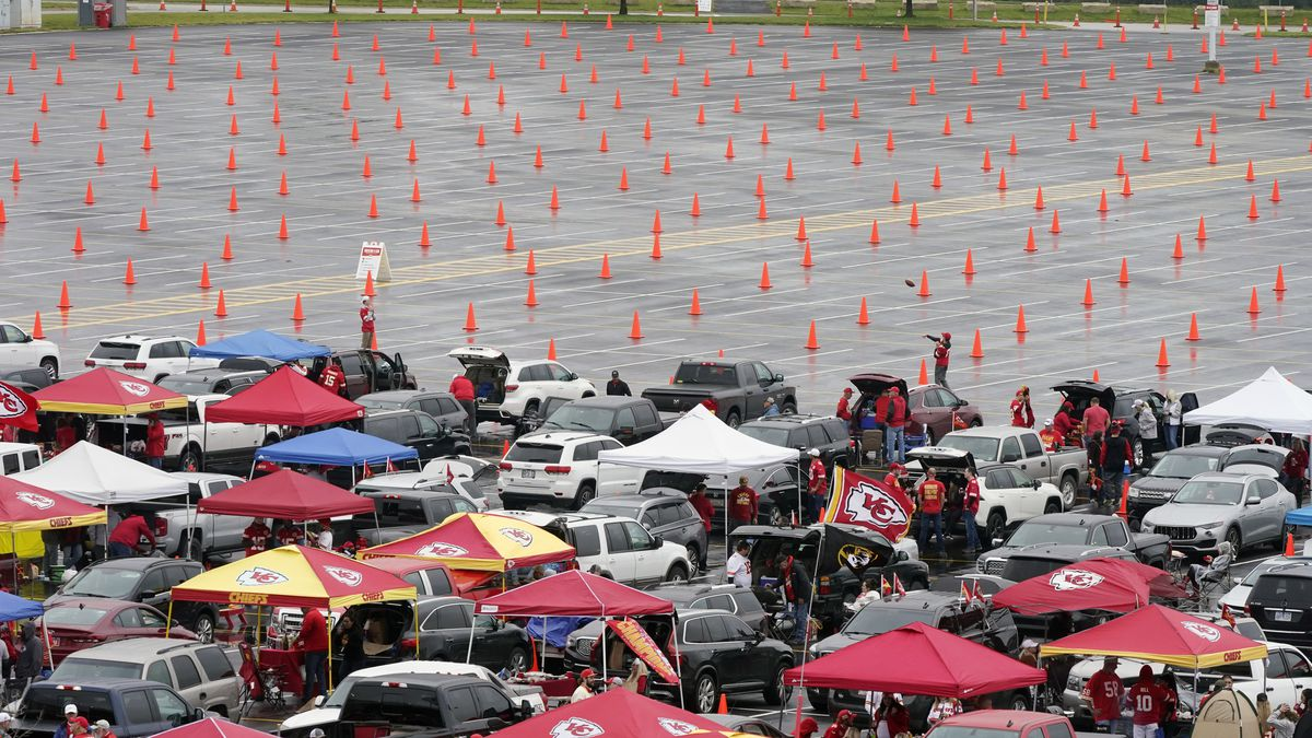 Fans tailgate in a partially filled parking lot outside Arrowhead Stadium before an NFL football game between the Kansas City Chiefs and the Houston Texans Thursday, Sept. 10, 2020, in Kansas City, Mo. (AP Photo/Charlie Riedel)
