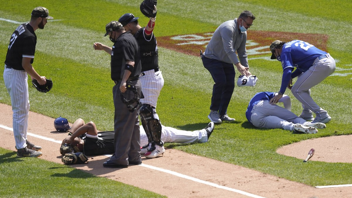 Chicago White Sox's Jose Abreu, left, and Kansas City Royals' Hunter Dozier lay near each other...