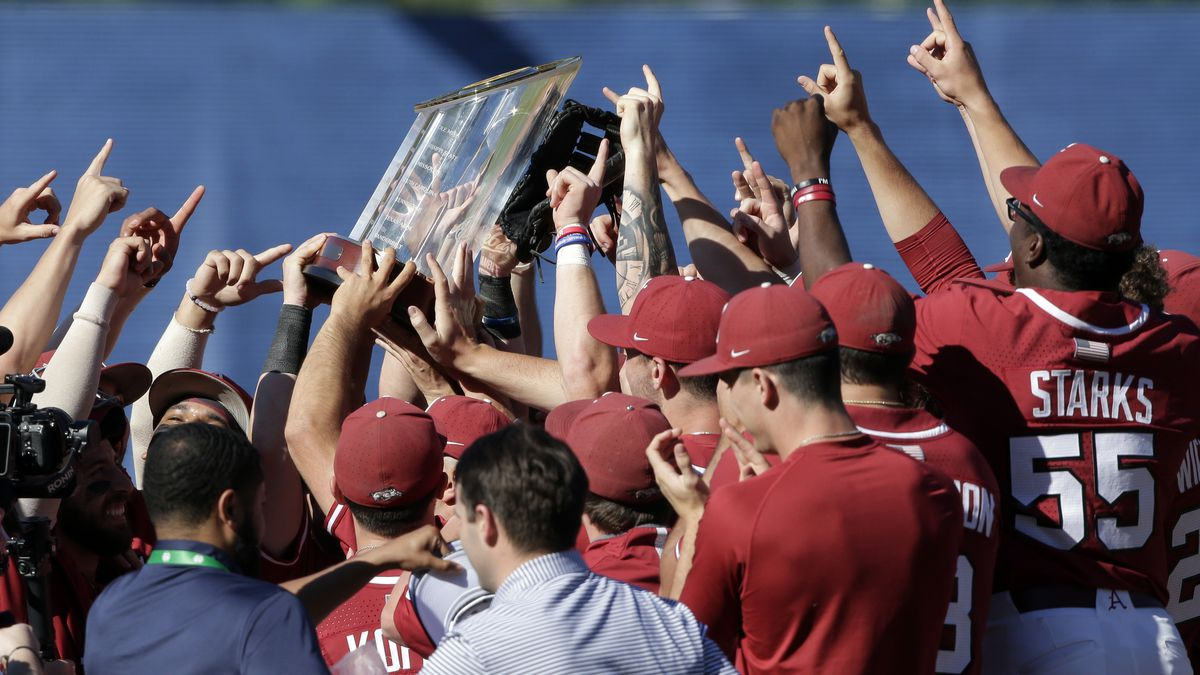 Arkansas players hoist the championship trophy after defeating Tennessee in an NCAA college...