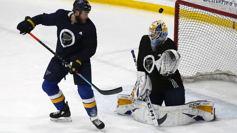St. Louis Blues' Ryan O'Reilly, left, watches a puck sail over goalie Joel Hofer during NHL...