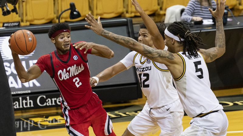 Mississippi's Devontae Shuler, left, passes the ball around Missouri's Mitchell Smith, right,...