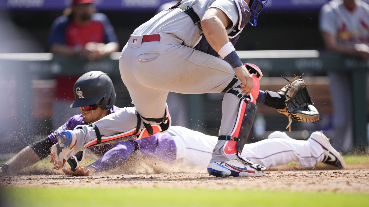 St. Louis Cardinals catcher Andrew Knizner, front, fields the throw as Colorado Rockies' Joshua...