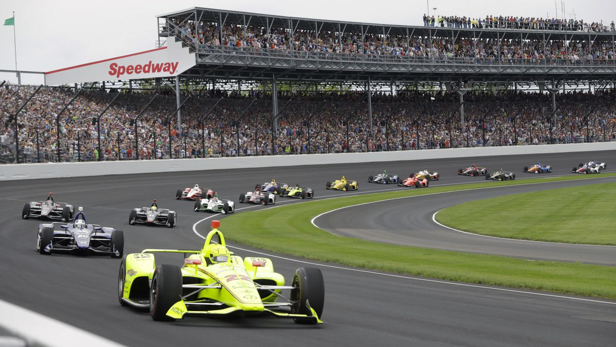 """In this May 26, 2019, file photo, Simon Pagenaud, of France, leads the field through the first turn on the start of the Indianapolis 500 IndyCar auto race at Indianapolis Motor Speedway in Indianapolis. Roger Penske has reversed course and decided not to allow fans at the Indianapolis 500 later this month. The 104th running of """"The Great American Race"""" will be the first without spectators, who showed up at Indianapolis Motor Speedway every year, even during the Great Depression."""