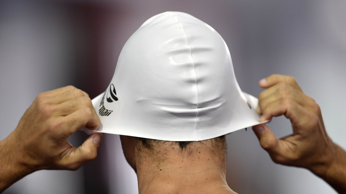 A swimmer prepares his cap during a training session at the 2016 Summer Olympics in Rio de...